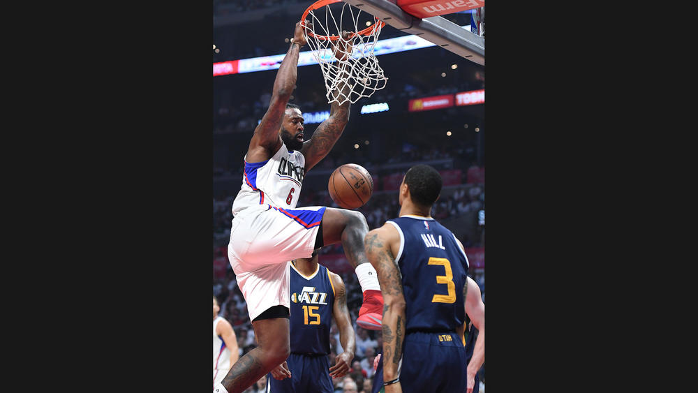 Clippers' center DeAndre Jordan slams home a dunk in font of the Jazz' George Hill in Tuesday night's game.