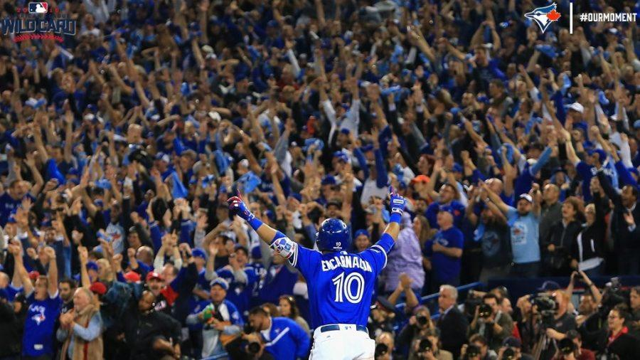 Blue Jays' first baseman, Edward Encarnarcion, lifts his arms in victory after hitting a walk-off home run in the bottom of the 11th inning.