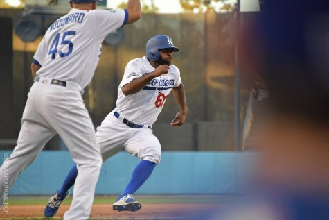 Dodgers' third base coach waves in Andrew Toles for the winning run in Tuesday's game against the Nationals.
