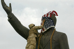 A United States marine drapes the face of a statue of Sadaam Hussein with an American flag April 2003.