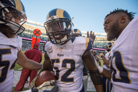 Teammates surround linebacker Alec Ogletree after he intercepts a pass in the final minutes of Sunday's game to secure the Rams' victory over the Jets.