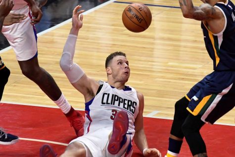 The Clippers' Blake Griffin falling to the ground while battling Jazz players for the ball.