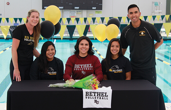 April 17- From left to right, Head coach Teddi Esko, Paula Alferez, Rachel Bustillos, Carleigh Cruz and Assistant Coach Anthon Salang are all smiles as Bustillos signs her National Letter of Intent to Bethel College, as well as two commitments to Hope International.
