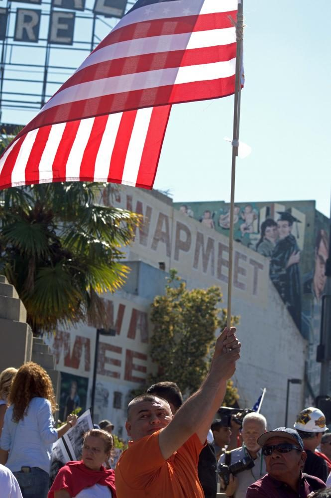 Anti-Trump Supporter displaying the American Flag as a symbol of Patriotism for undocumented immigrants on May 1st in MacArthur Park
