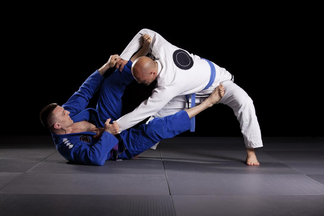 Two jiujitsu wrestlers sparring in combat during the sport training.