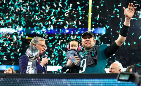 Super Bowl LII MVP Nick Foles salutes the Minneapolis crowd as confetti falls on him and his daughter.