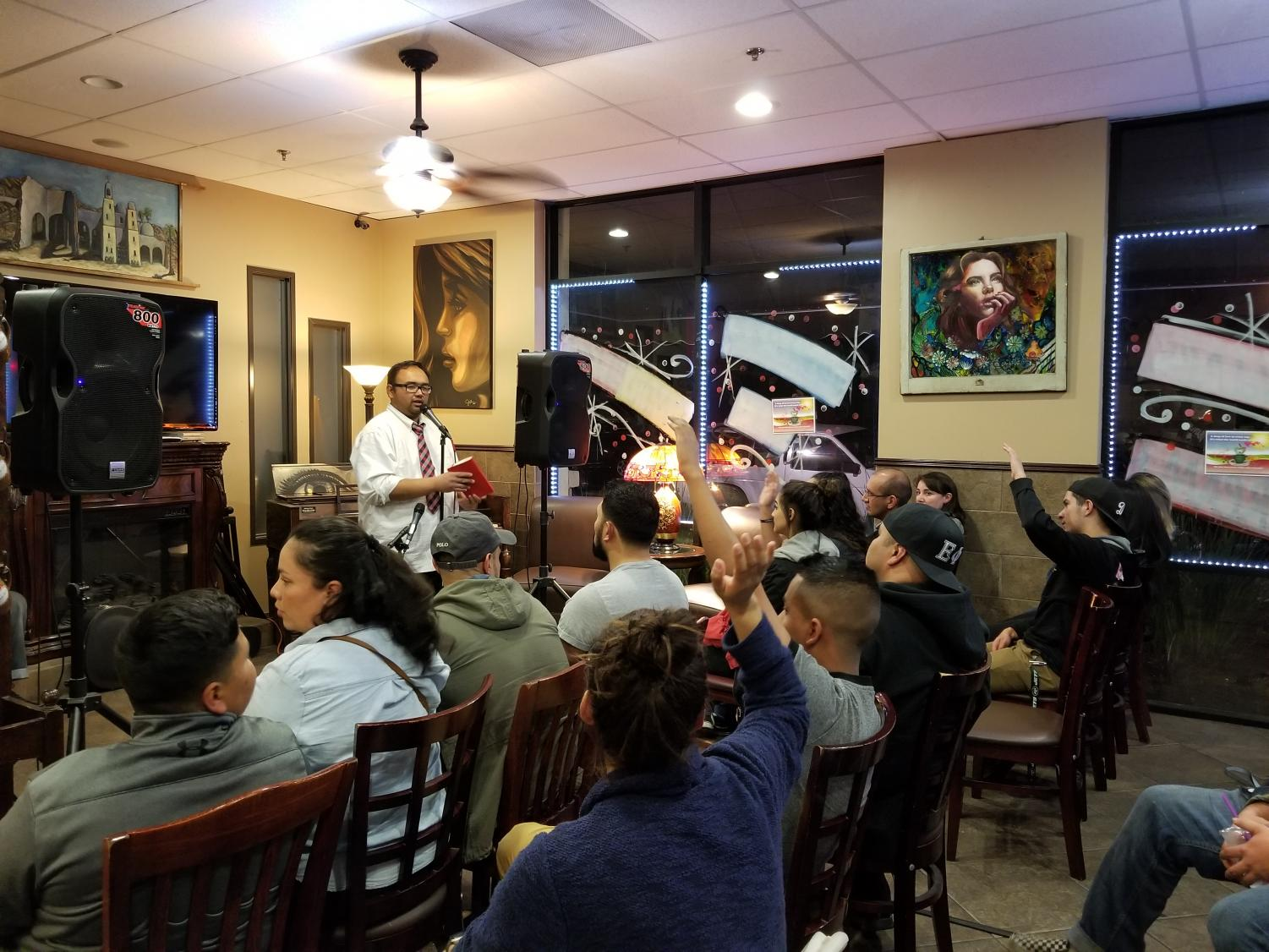 One of the hosts of the Daily Brew Open Mic, K.P., addresses the audience at a Wednesday night show. Members of the audience raise their hands to show their support.