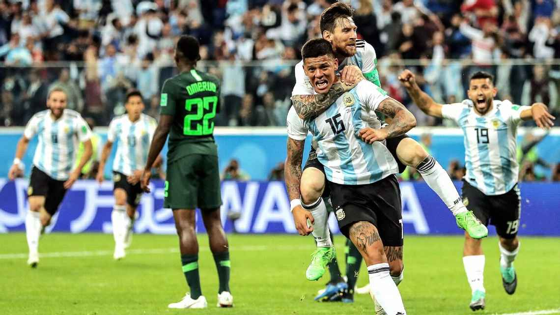 Lionel Messi piggy-backs Marcos Rojo (no. 15) after the latter's goal kept Messi from backing his bags. Photo credit: Richard Heathcote, Getty Images