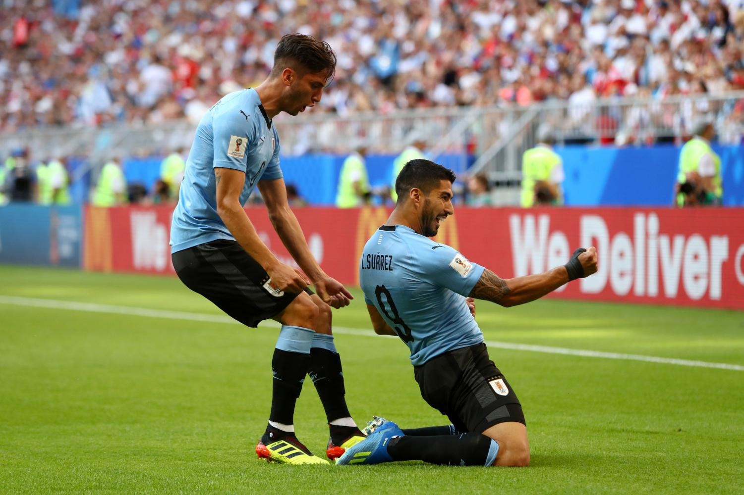 Luis Suarez celebrates his second goal of the tournament as his free kick earned Uruguay top slot in Group A.Photo credit: Dean Mouhtaropoulos/Getty Images.