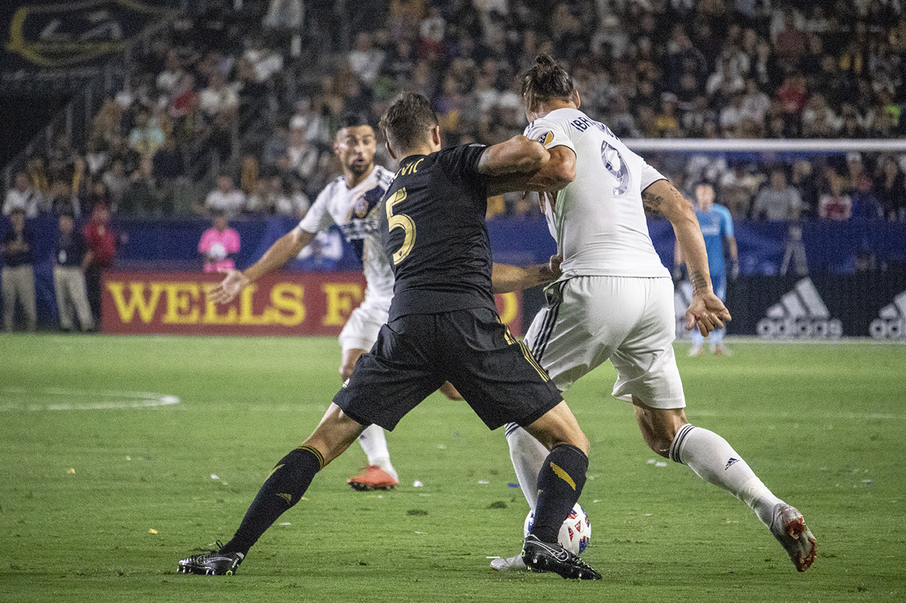 Dejan Jakovic attempts to fend-off Zlatan Ibrahimovic during LAFC's visit to StubHub Center to face the Galaxy. Photo, Andres Martinez.