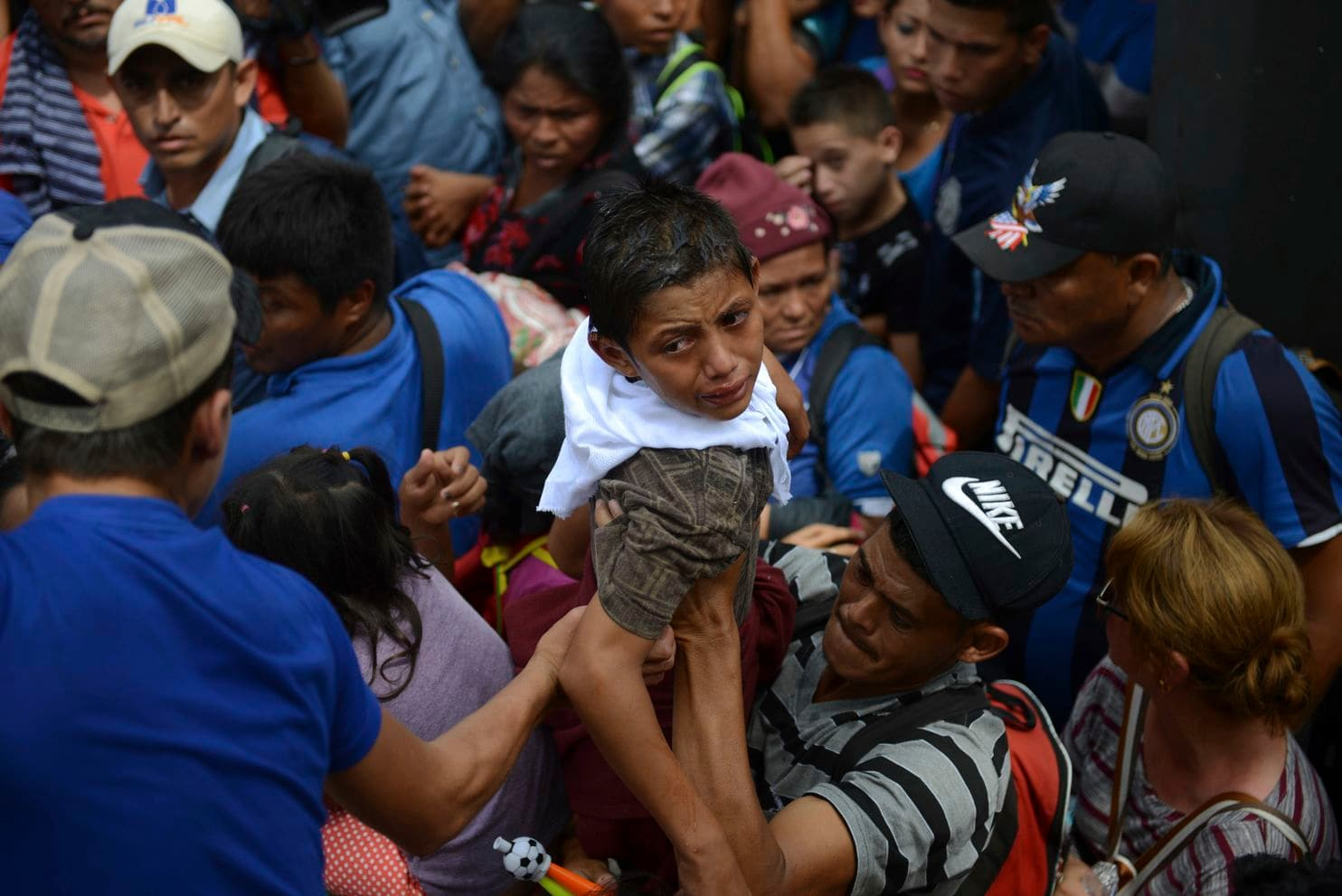 A boy cries as he is brought back down after an unsuccessful attempt to lift him over a border fence, in Tecun Uman, Guatemala, Friday, Oct. 19, 2018. Earlier in the day, waving Honduran flags and carrying umbrellas to protect against the sun, thousands of migrants arrived at the Guatemalan side of the border with Mexico, demanding they be allowed passage.