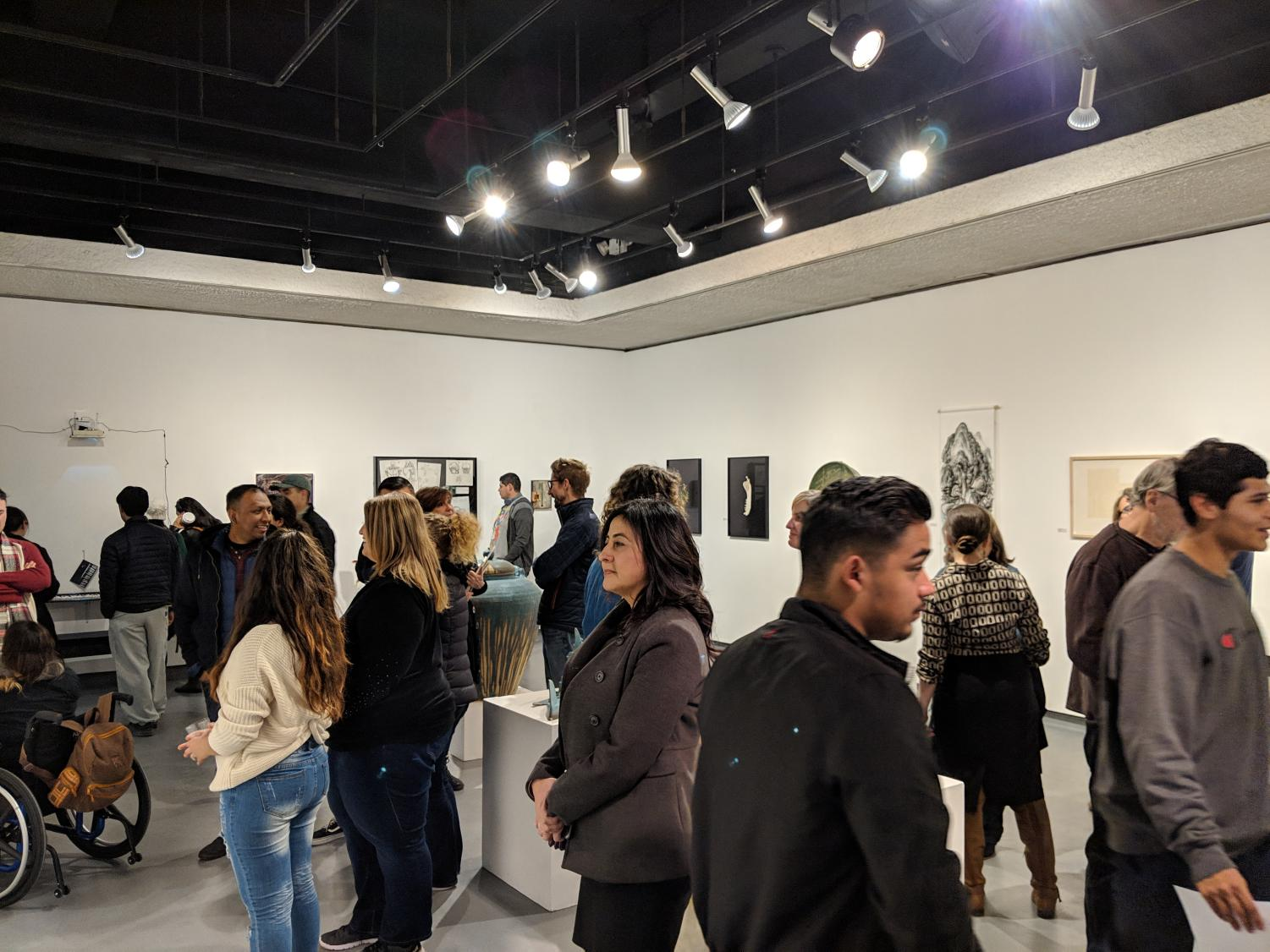 Before commencing the art show, Art Gallery Director Robert Miller advised those who were present to be cautious of the art pieces displayed in the middle of the show floor. Students who took time from their classes to attend the show listened to the interesting backstories that accompanied the art pieces.