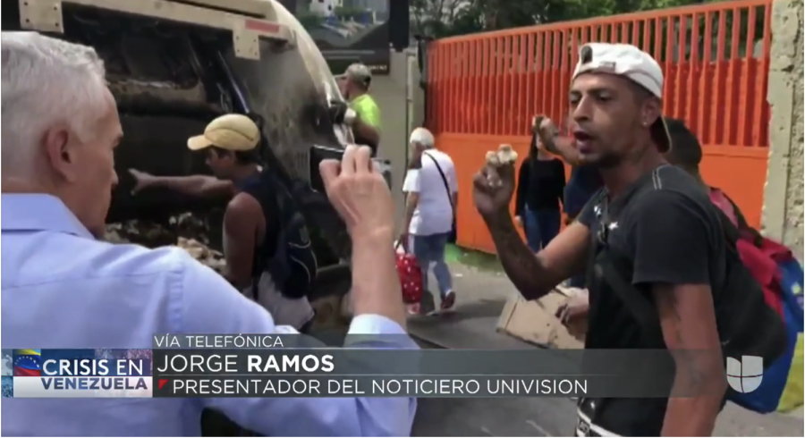 Jorge+Ramos+recording+young+Venezuelan+men+picking+food+out+of+the+back+of+a+trash+truck.+It+was+this+image+that+pushed+President+Nicolas+Maduro+over+the+edge+and+detained+the+six+Univision+reporters+and+confiscated+their+equipment.