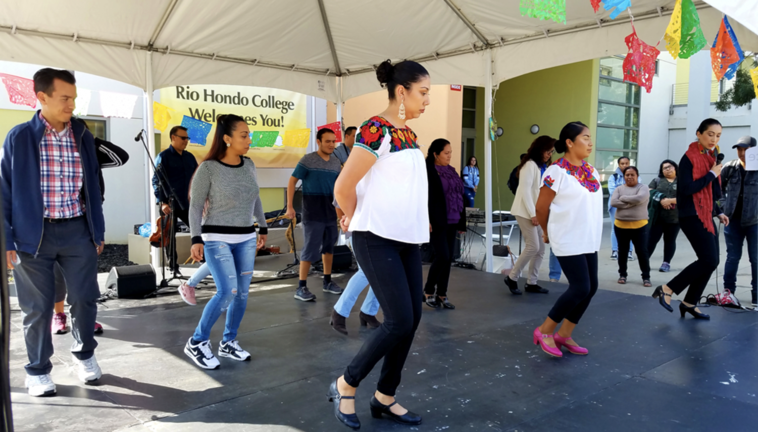 Dr. Argelia Andrade (far right) teaches students choreography for Mexican folk song,